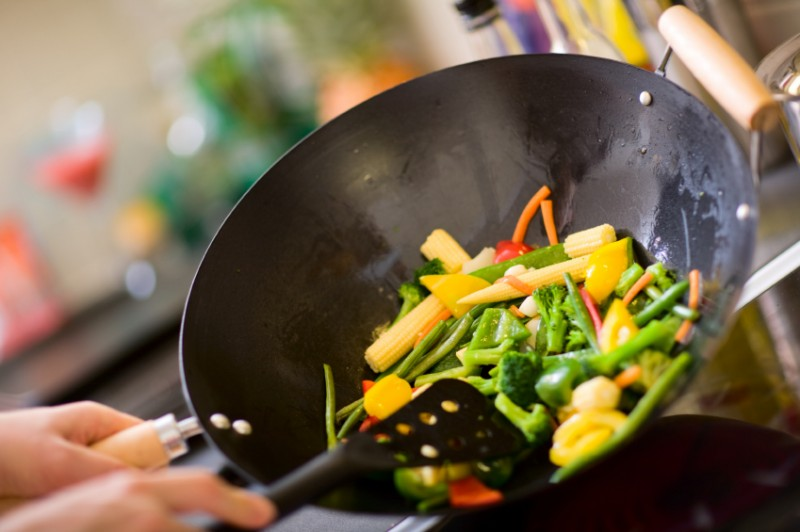 Chef cooking vegetables in wok pan